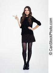 Smiling girl pointing finger away - Full length portrait of...
