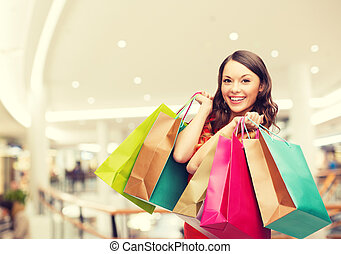 smiling young woman with shopping bags - happiness,...