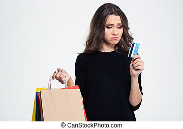 Sad woman holding shopping bags and bank - Portrait of a sad...