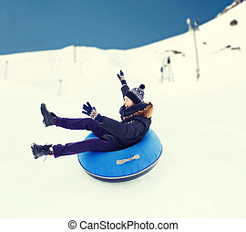 happy young man sliding down on snow tube - winter, leisure,...
