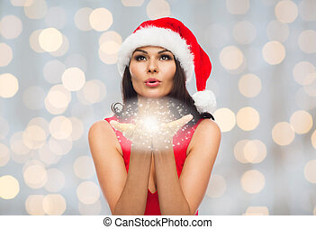 beautiful sexy woman in santa hat blowing on palms - people,...