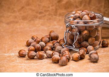Unpeeled hazelnuts in glass jar