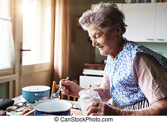 Senior woman baking pies in her home kitchen Measuring...