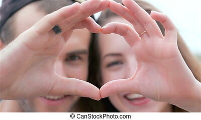 Couple of lovers looking at the camera and show heart
