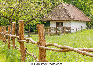 Old rural house with wooden fence