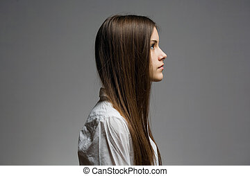 Stand straight. - Expressive profile of young brunette.