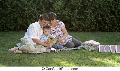 family sitting in the summer park