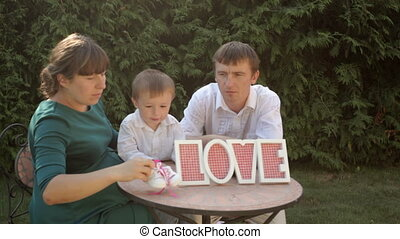 young family sitting at a table with a sign Love