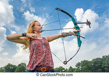 Young woman shooting archery with compound bow and arrow -...