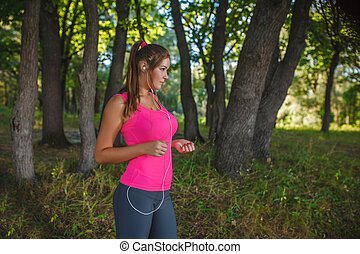 Girl European appearance in a pink shirt and gray tights listening to music on headphones white running through the woods, nature, running, sports