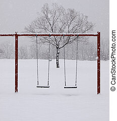 Playground in Winter - Snow covered swing-set with tree in...