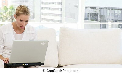 Happy businesswoman working at laptop sitting on sofa