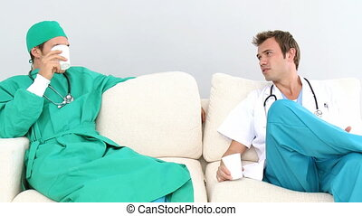 Two male doctors sitting on a sofa in a staff room