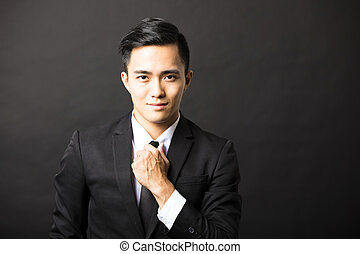young asian businessman on black background