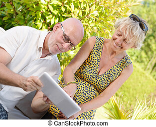 middle age couple, smiling, using a tablet in their garden