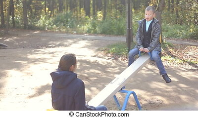 Boy and girl singing on swings in the park