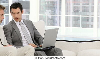 Business group working at a laptop sitting on sofa