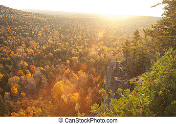 Backlit cliff and pines with lens flare above trees in fall color on Oberg Mountain in northern Minnesota