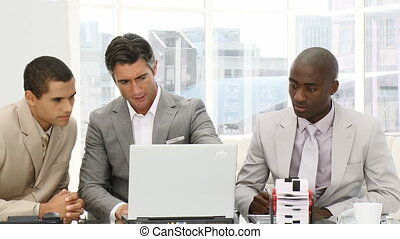 Serious businessmen working at a computer in a meeting
