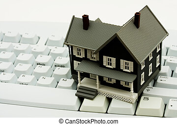 Online Real Estate - A model house sitting on a computer...