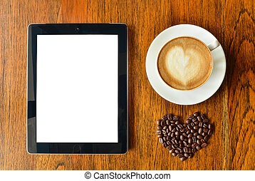 Digital tablet pc and a cup of coffee with heart shape on wood background