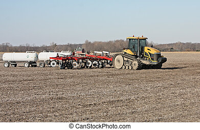 Farm Tractor - Farm tractor in a field pulling a disc and...