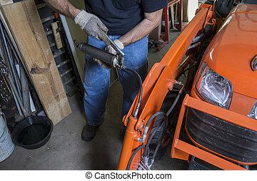Mechanic Using A Grease Gun - Mechanic using a grease gun to...