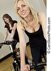 Two Beautiful Young Women On Exercise Bikes At The Gym