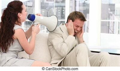 Young businesswoman yelling through a megaphone in her...