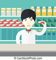 Pharmacist - An asian pharmacist at the counter in a...