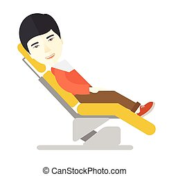 Patient in dental chair. - An asian patient sitting in the...