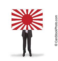 Smiling businessman holding a big card, flag of Japan,...