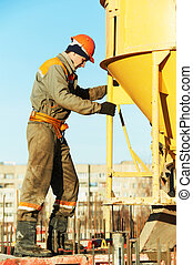 building worker pouring concrete with barrel - building...