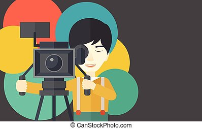 Cameraman. - An asian cameraman looking through movie camera...
