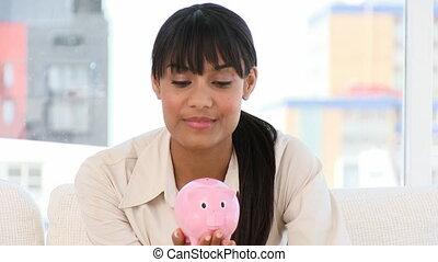 Ethnic businesswoman holding a piggy-bank at work