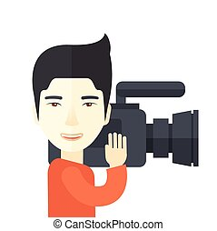 Cameraman. - An asian cameraman with video camera taking a...