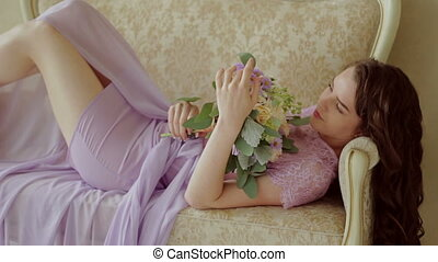 Lovely young girl lying on the couch with a bouquet of flowers
