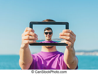 Man doing a self-portrait with him digital tablet on beach -...