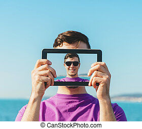 Man doing a self-portrait with him digital tablet - Young...