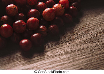 Red gooseberries on wooden background, space for text in...