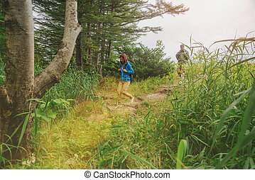Couple of hikers walking down from hill in summer forest