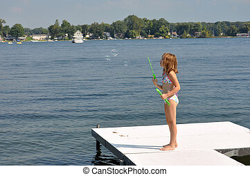 bubbles at the lake - a young girl shows off her bubble...