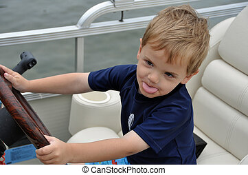 sassy captain of the boat 2 - a cute little boy drives a...