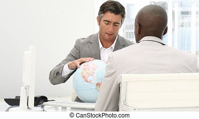 A meeting of businessmen around a terrestrial globe against...