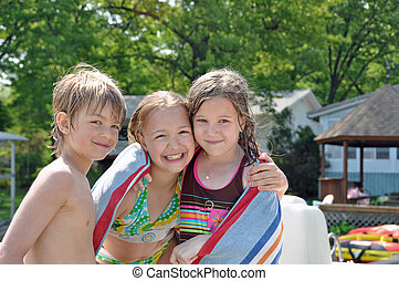 swimming buddies - three children dry off after spending the...
