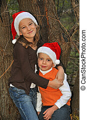 santa hats in the woods 3 - two children pose by a tree...