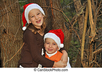 santa hats in the woods 2 - two children pose by a tree...