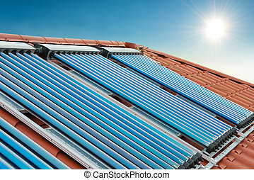 Vacuum collectors- solar water heating system on red roof of...