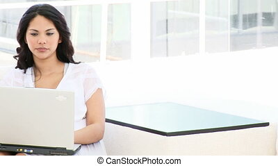 Young business woman working at a laptop sitting on sofa
