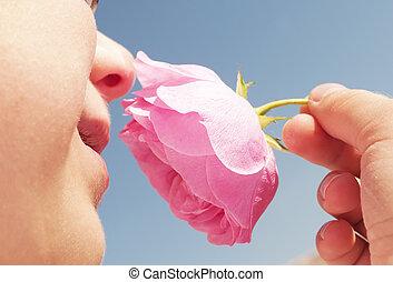 boy smelling pink rose
